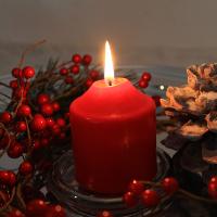 Rote Kerze mit Tannenzapfen