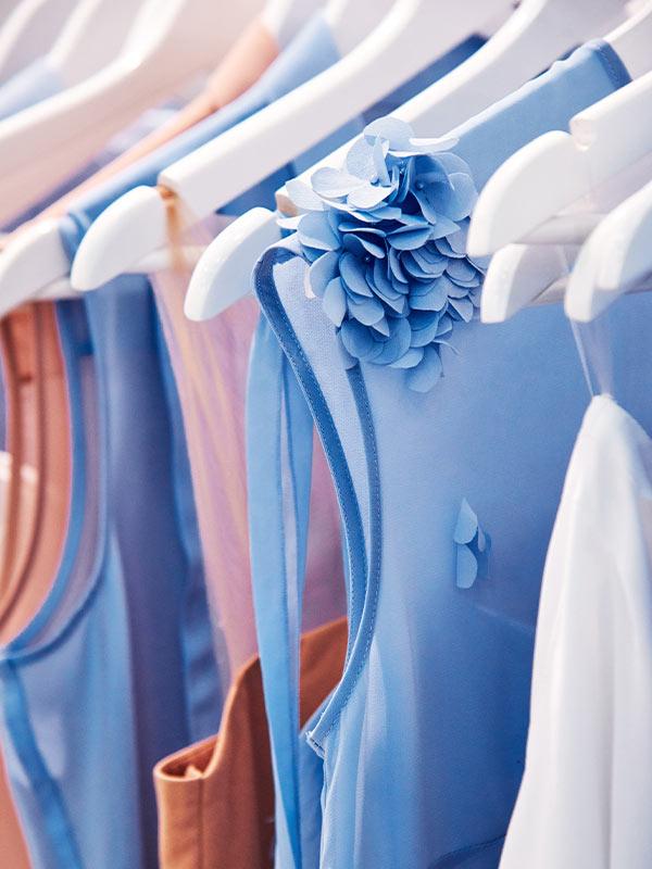 Kleider ordentlich auf Buegel gehaengt