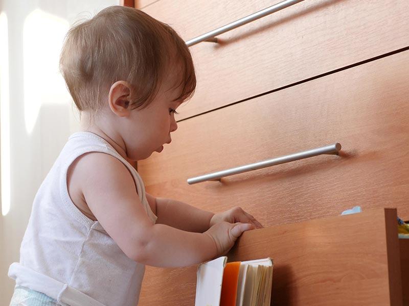 Kind vor Schubladenschrank