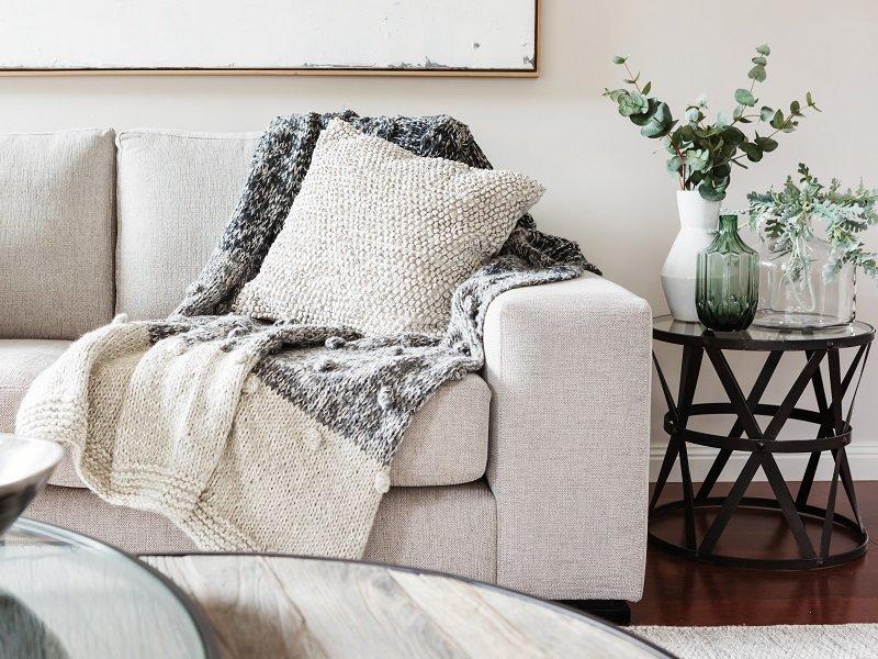 Sofa mit hellen Kissen und Decken.