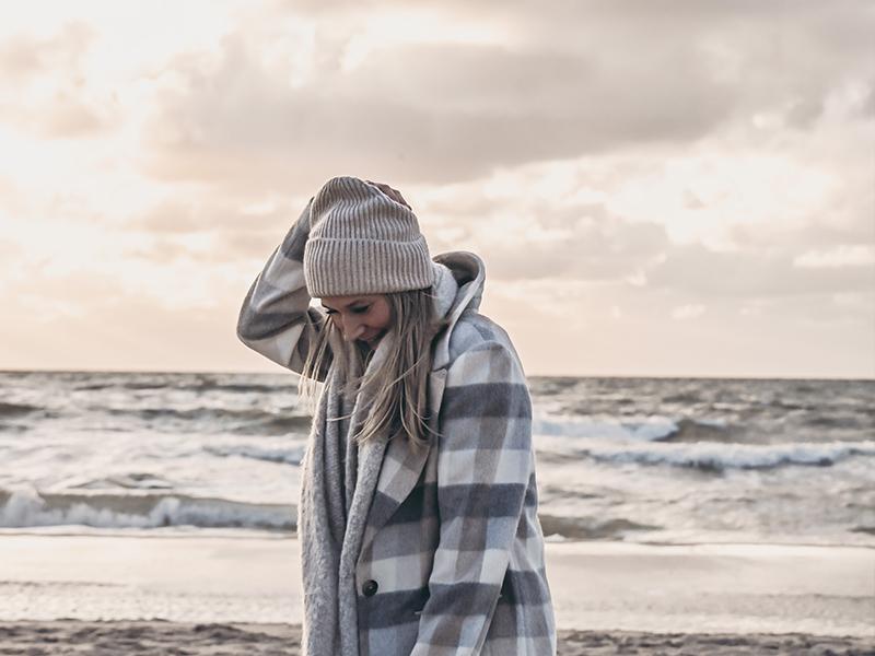 Instagram Interior Account: Bloggerin sardoe mit Jacke und Mütze am Strand